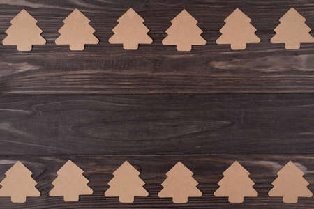 Top above overhead view flat lay photo of rows of christmas tree shaped paper decorations isolated on wooden background with copyspace Stock Photo