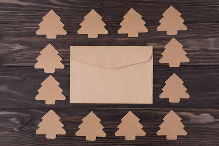 Top above overhead view flat lay photo of christmas tree shaped paper decorations making a square with envelope in center isolated on wooden background with copyspace Stockfoto
