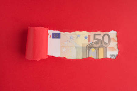 Top above overhead view photo of torn red paper over 50 euro bill with copyspace Stock fotó
