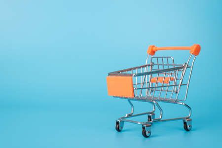Closeup photo of small mini shopping cart with orange handle isolated over light color blue background with blank space 版權商用圖片 - 157483680