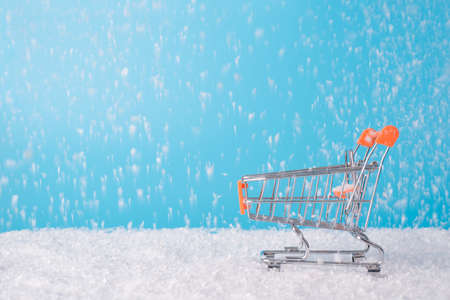 Merry shopping weather concept. Close up side profile view photo of little miniature silver trolley cart and falling snow