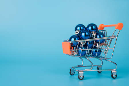 Full length size photo of small metal silver trolley cart full of little toy dark blue baubles isolated of pastel color blue background