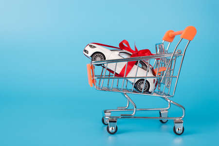 Side full length profile photo of small toy miniature automobiles with red ribbon carried by trolley cart isolated over blue color background