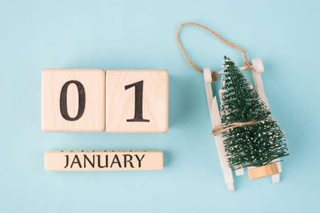 New Year is here concept. Top above overhead view photo of wooden cubes showing the first day of the year and little christmas tree on sledge isolated on light blue background Stok Fotoğraf