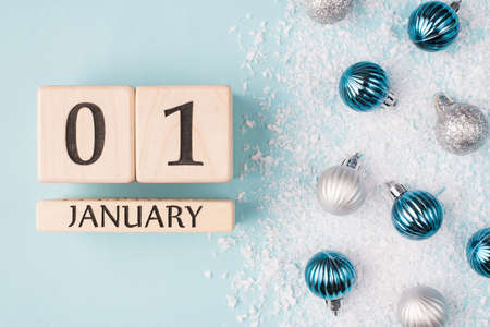 New Year concept. Top above overhead view photo of wooden cubes showing the first day of new year isolated on blue background with snow and baubles Stok Fotoğraf