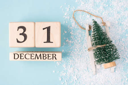 Top above overhead view photo of wooden cubes showing the last day of the year and little christmas tree on sledge isolated on light blue background with snow