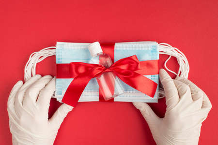 Deliver presents concept. First person top view close up photo of hands in white rubber gloves holding packing masks and antibacterial gel isolated bright red color background