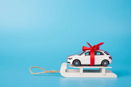 Winter sale concept. Present concept. Close up full length size photo of toy white car in with red ribbon on white wooden sledge isolated on blue background with copyspace