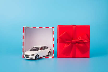 Giving and receiving gifts concept. Close up photo of white toy car in open red giftbox with bow isolated on blue background Stock Photo