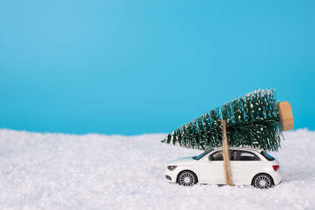 Christmas preparations concept. Close up photo of toy mini car carrying little christmas tree on top isolated on blue background