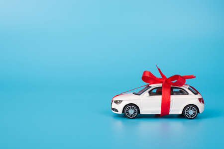Present concept. Close up full length size photo of toy white car in with red ribbon isolated on blue background with copyspace