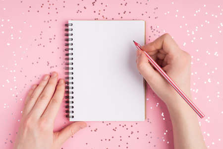 Close up top above overhead first person view photo of teen teenager hands holding pencil and clean page of notepad on girly pink background