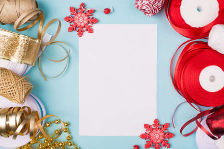 New year resolution concept. Top above overhead close up view photo with wrapping tap ribbon accessories and blank empty page on blue desk table with toy snowflakes