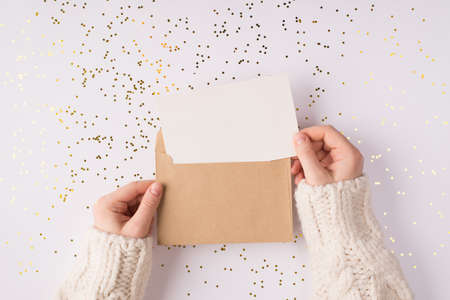 Top above close up overhead view photo of female hands holding kraft paper envelope with mock up copy space card inside over shiny golden background table Foto de archivo