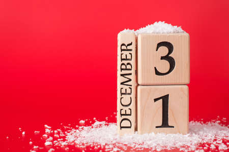 The last day of year concept. Close up photo of wooden cubes calendar showing the last date of year isolated on red background with snow Stock Photo