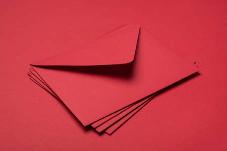 Top close up layout flat lay view photo of heap of red bright envelopes isolated on vivid background table