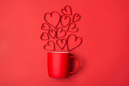 Love in the air breakfast on valentines day concept. Above overhead view photo of bright red cup with flying hearts isolated bright color background