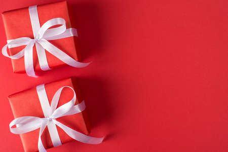 Above close up view photo of two present boxes tied with white silky ribbon isolated red color bright background with copy space
