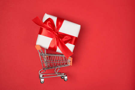 Top above flatlay close up profile view photo of metal silver trolley basket on wheels carrying big present box isolated red bright color background 写真素材
