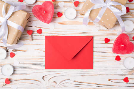 Invitation on marriage concept. Top above close up view photo of border valentines day composition and red envelope on textured wooden background