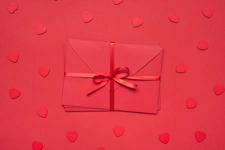 Top above close up view photo of heap of bright red envelops wrapped tied with ribbon isolated ob vivid color background with heart shaped serpentine