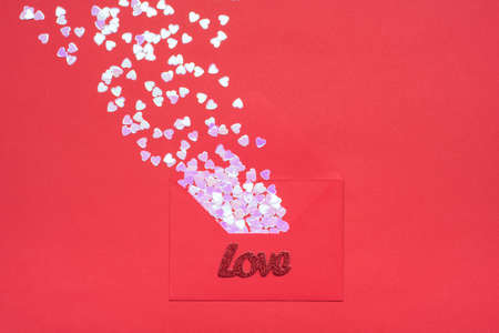 Layout flatlay close up view photo of open red envelope and flying away sequins in white color in shape of hearts isolated monochrome minimal backdrop