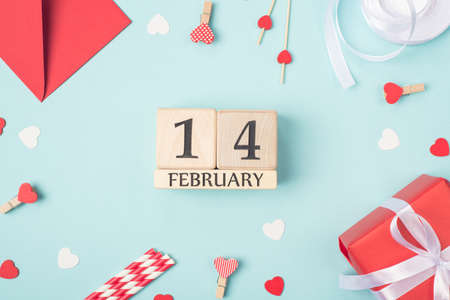 Overhead close up view photo of 14 february on wooden cube shape calendar and valentine day accessories around
