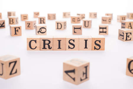 Crisis concept. Close up view photo of wooden blocks making word crisis isolated white backdrop table 写真素材