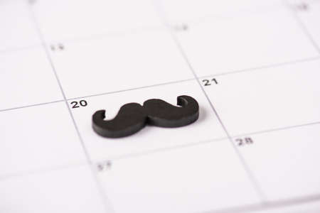 Happy Father's day concept. Close up photo of black mustache marked lying on calendar cell