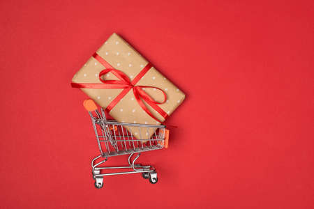 Top flatlay view photo of mini trolley basket with wrapped present box inside isolated over bright red color background 写真素材