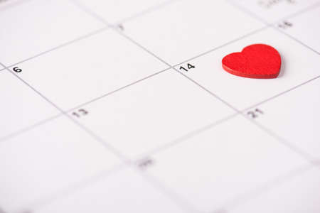 Valentine day celebration concept. Close up view photo of calendar with lying on it red heart on 14th february 写真素材