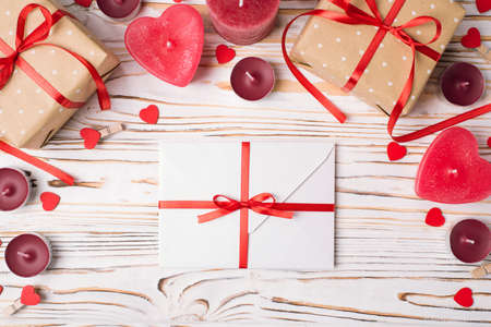 Top above overhead close up border view photo of st valentines day ornament composition and white envelope wrapped tied with red bright color ribbon