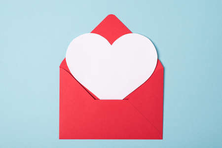 Close up view photo of open red envelope and white heart shaped greeting card isolated light pastel color background