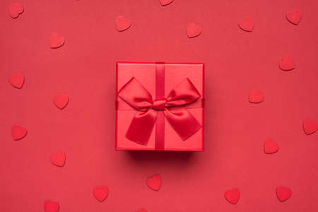Happy saint valentines day. Photo overhead of cute present wrapped box with ribbon and bow isolated monochromatic red background 写真素材