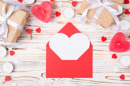 Top close up above overhead view photo of valentines day composition and open red envelope with white card inside in shape of heart 写真素材