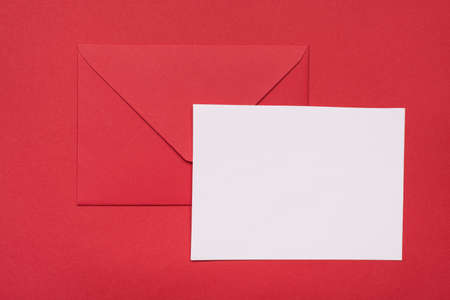 Close up view photo of red color envelope and white blank empty sheet of paper isolated bright red color background