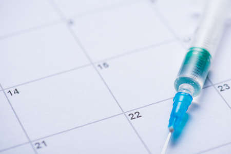 SarsCov-2 vaccination reminder concept. Cropped close up view photo of syringe with transparent liquid lying on calendar with written dates