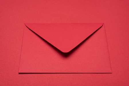 Close up view photo of bright red paper monochromatic envelope isolated vibrant color backdrop table 写真素材