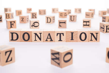 Donation concept. Close up view photo of wooden cubes making showing donation word isolated white backdrop