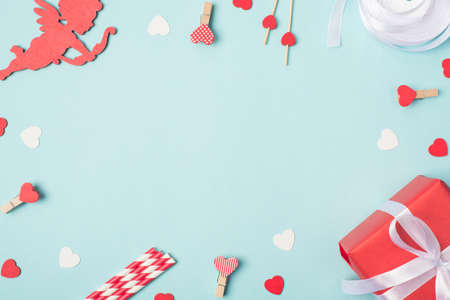 Happy valentines day concept. Photo above image of red and white decorations little cupid wrapped package and heart pins on light background with empty space