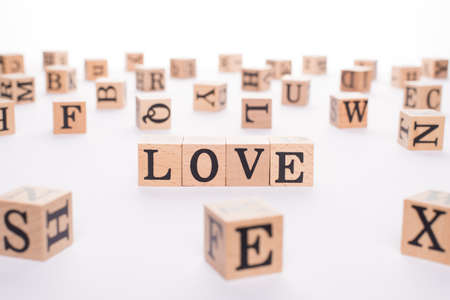 Love and sex concept. Close up view photo of wooden cubes making showing word love on white desk table