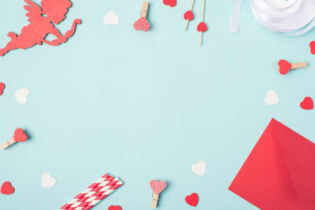 Flat lay mock up photo image of lovely cupid pins with red and white hearts envelope on pastel blue table backdrop 写真素材