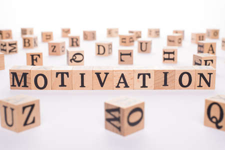 Motivation concept. Close up view photo of wooden cubes making showing word motivation on white background
