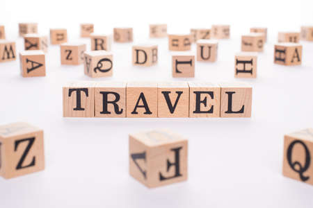 Travel concept. Close up view photo of wooden cubes making showing word travel isolated white background 写真素材