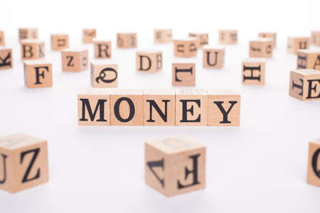Money concept. Close up view photo of wooden cubes making showing word money isolated white desk backdrop