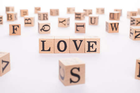 Love concept. Close up view photo of wooden cubes making showing word love on white table desk