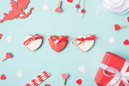 Flatlay close up photo image of yummy cookies in shape of hearts with wishes on rolled papers on blue desk with gift package little heart pins 写真素材