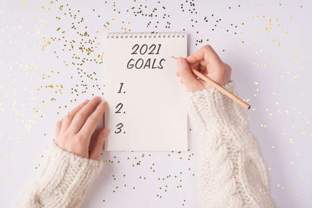 Top overhead above close up flatlay view photo of female hands making noted to the open notebook with inscription 2021 goals