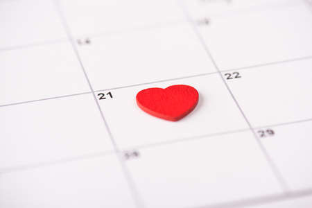 Doctor appointment concept. Close up photo of red heart lying on calendar on the 21 date on calendar