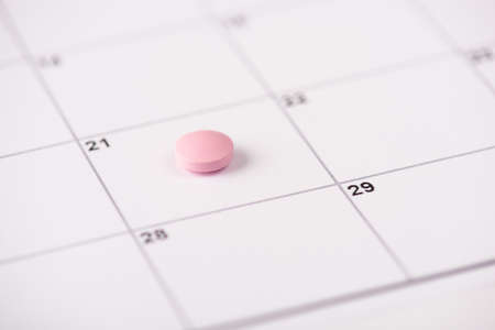 Taking drugs in time concept. Close up view photo of pastel light color pink pill lying on white calendar cell